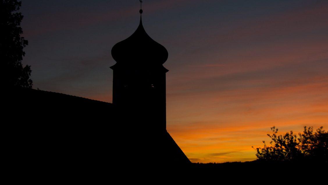 Die Kirche zu den Heiligen Gräbern in Walkersbrunn im Gegenlicht des Sonnenuntergangs